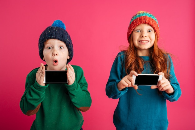 Two little excited children showing displays of mobile phones.
