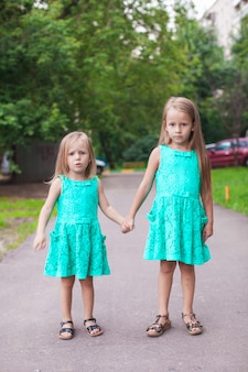 Two little fashion sister walking together on street