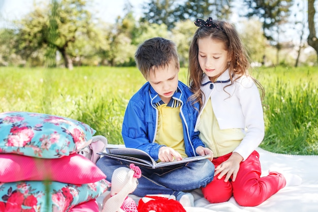 Two little friends read a book in the park. concept of education