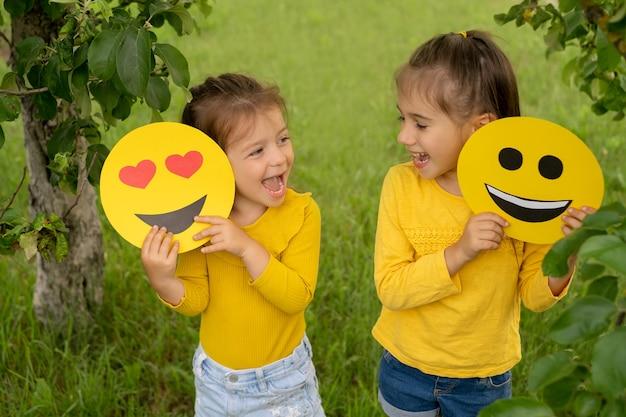 2人の小さな面白い女の子が手にさまざまな感情を持つ笑顔を持っています