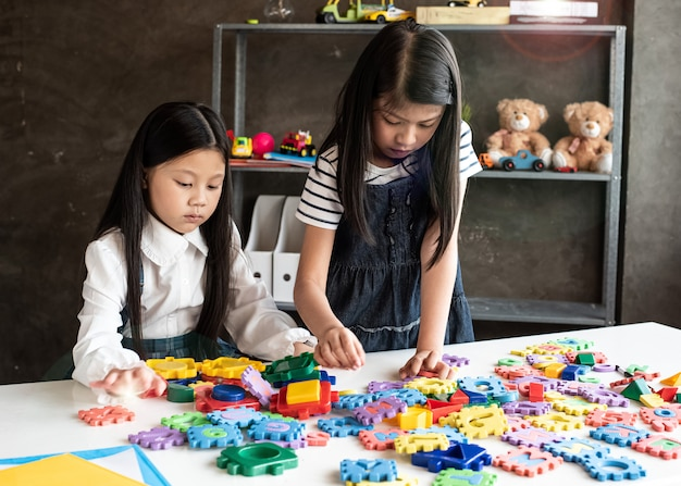 Two little girl are playing plasticine together,with interested feeling,at home studio,lens flare effect,blurry light around