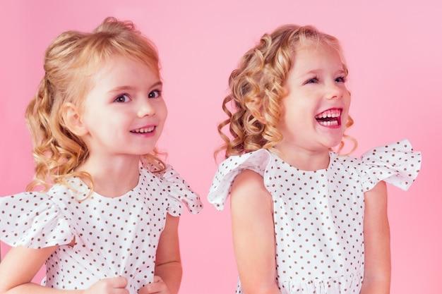 2つの小さな女の子の美しさの女王の青い目、ピンクの背景のスタジオでポーズをとるエンドウ豆のかわいい白いドレスで彼女の頭にティアラの王冠を持つブロンドの髪型をカールします。誕生日のお祝い、美人コンテスト。