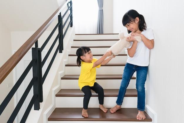 Two little girl fighting over bear