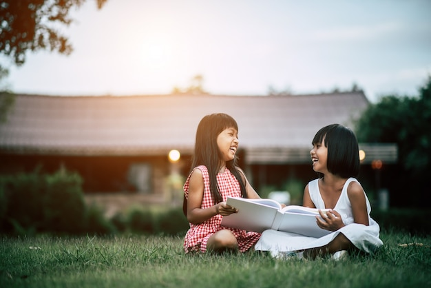 Two little girl friends in the park on the grass reading a book and learn
