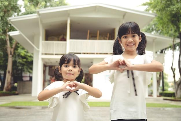 Two little girl hands making a heart shape