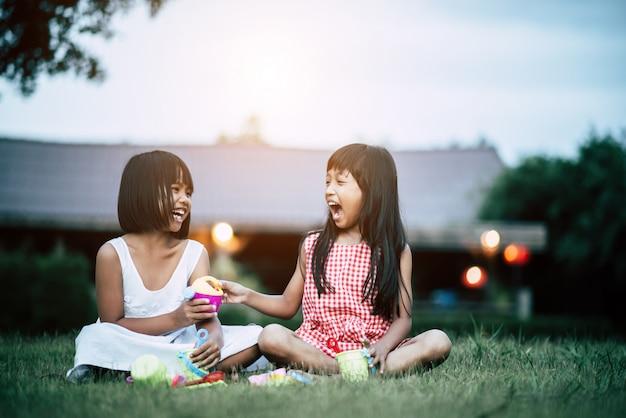 2人の少女は家の庭でおもちゃをする