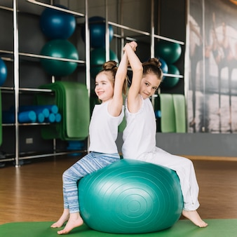 Two little girl sitting back to back on exercising ball together