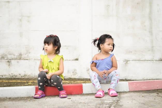 Two little girl sitting on different sides not looking at each other and not talking