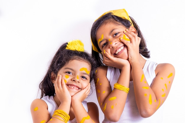Two little girl, with her face painted to celebrate the yellow day