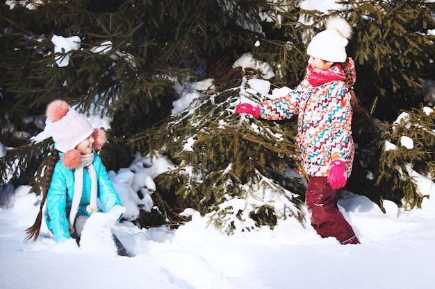 2人の少女がウィンターパークで遊んでいます