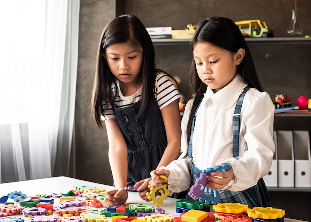 Two little girls are playing plasticine together,with interested feeling,at home studio,lens flare effect,blurry light around