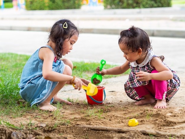 Two little girls are playing sand in the park.