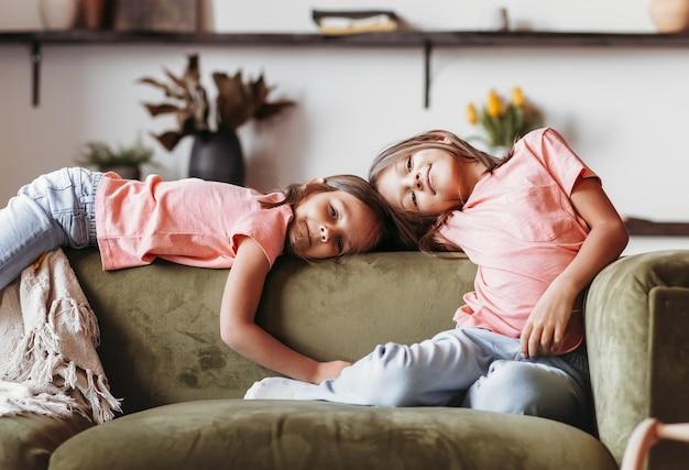 두 소녀는 거실의 소파에서 휴식을 취하고 있습니다. 자매들은 함께 시간을 보냅니다. 아이들의 우정