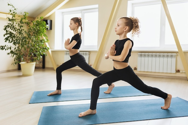 Two little girls in black leggings and tops practicing yoga in the studio perform virabhadrasana warrior pose