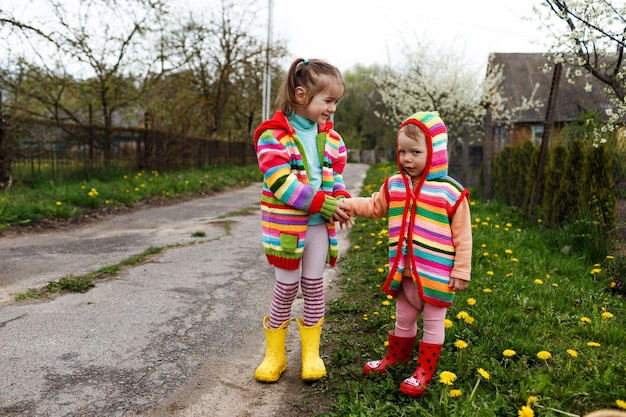Two little girls in bright clothes hold each other's hands among the yellow dandelions. happy childhood.