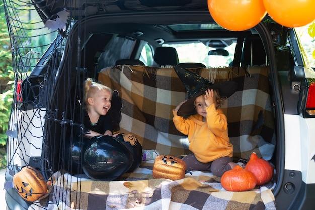 Two little girls celebrating halloween car trunk safe autumn holidays