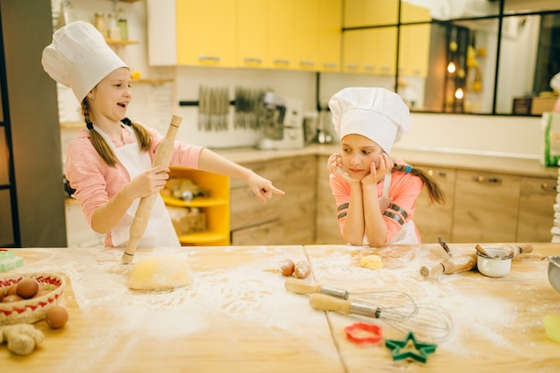 Two little girls chefs are laughing, cookies preparation on the kitchen. kids cooking pastry and having fun, children cooks preparing cake, happy childhood
