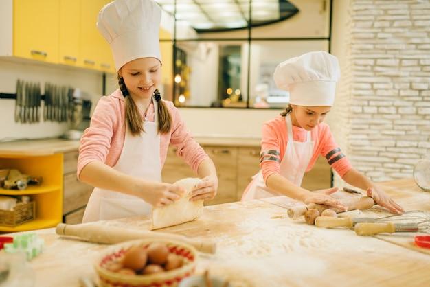 2人の少女シェフが麺棒で生地を伸ばす