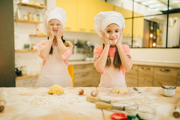 Two little girls chefs smears their faces with flour