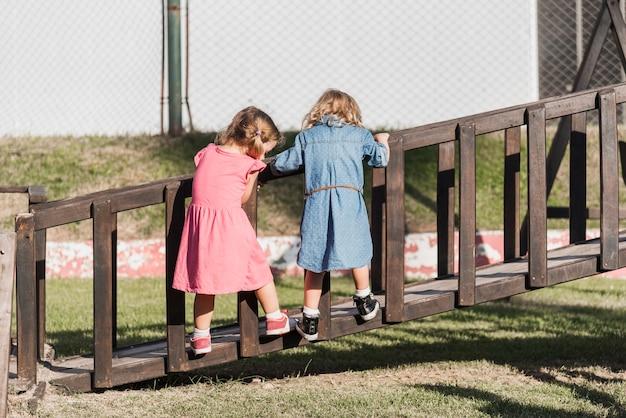 Two little girls climbing on boardwalk