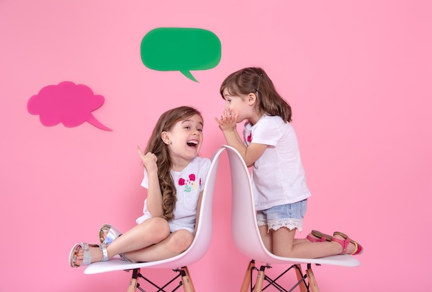 Two little girls on colored wall with speech icons