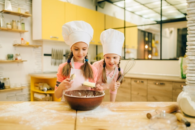 Two little girls cooks in caps adds butter to the bowl, cookies preparation on the kitchen. kids cooking pastry, children chefs makes dough, child preparing cake