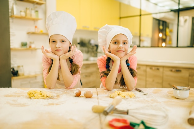 Two little girls cooks in caps are sitting at the table, cookies preparation on the kitchen. kids cooking pastry, children chefs preparing cake