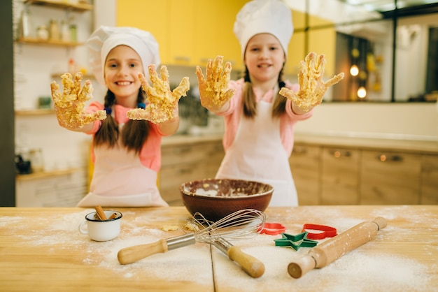 Two little girls cooks in caps shows hands covered in dough, cookies preparation on the kitchen. kids cooking pastry, children chefs makes dough