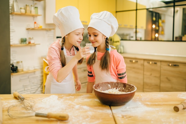 Two little girls cooks in caps sniffing sweet vanilla powder, cookies preparation on the kitchen. kids cooking pastry, children chefs preparing cake