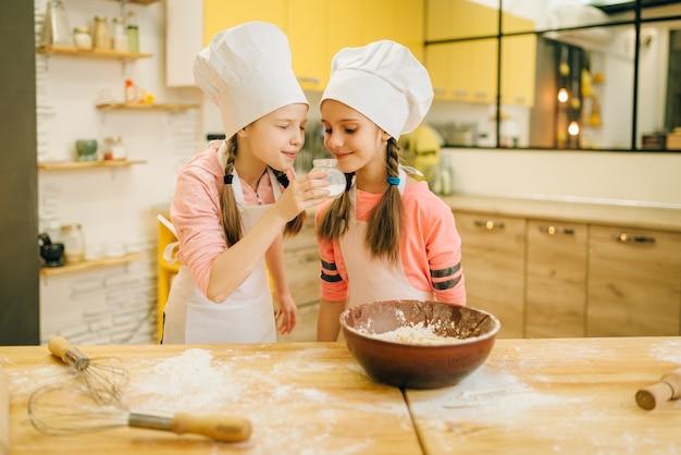 두 어린 소녀는 달콤한 바닐라 가루를 냄새 맡는 모자, 부엌에서 쿠키 준비를 요리합니다. 과자를 요리하는 아이들, 케이크를 준비하는 어린이 요리사