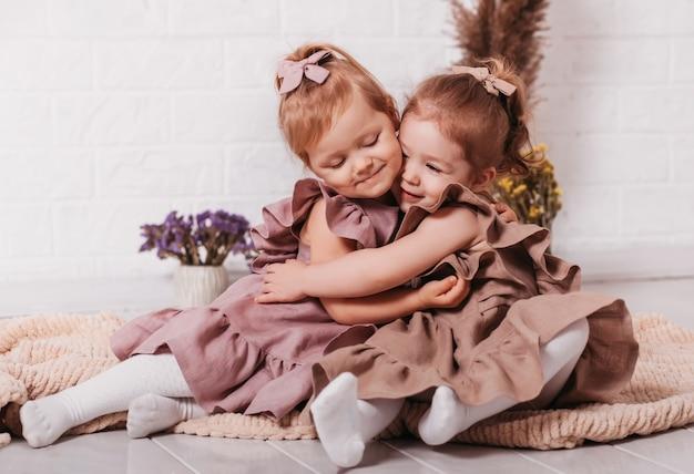 두 어린 소녀가 바닥에 피그 테일을 껴안고 웃습니다.