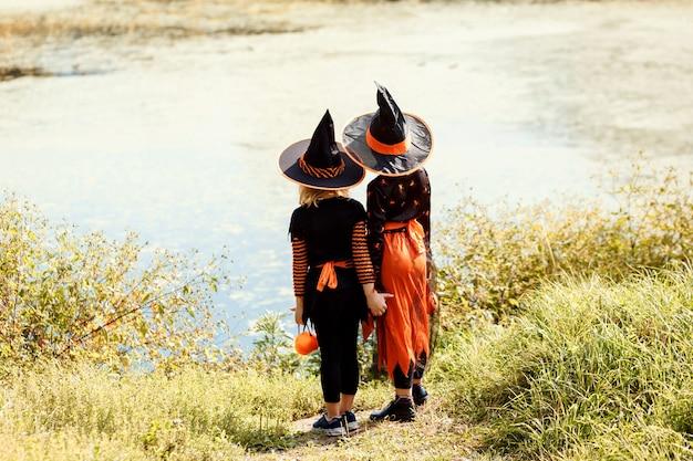 屋外の池の隣に立っている魔女としてカーニバルのハロウィーンの衣装を着た2人の少女...