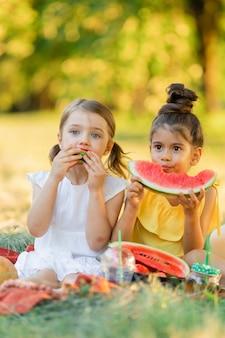 庭でスイカを食べる二人の少女子供たちは屋外で果物を食べる子供のための健康的なスナック
