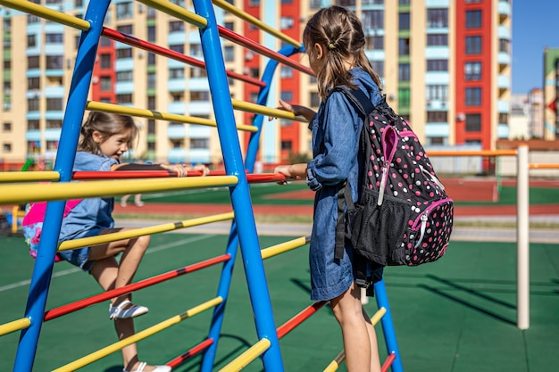 Two little girls, elementary school students, play on the playground after school.