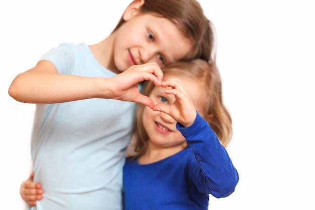 二人の少女が手でハートを形作る