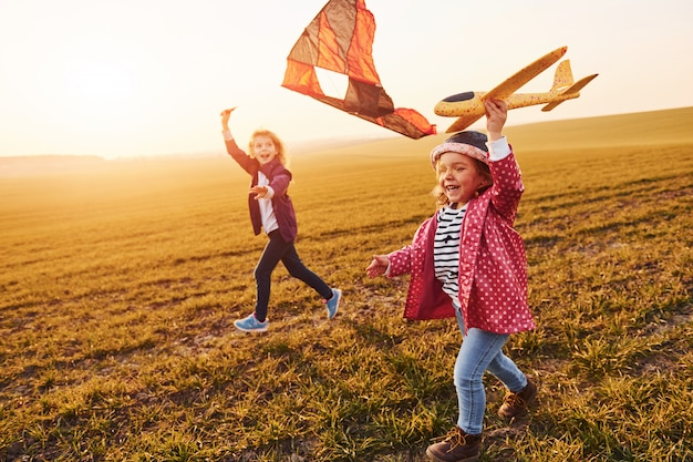 Two little girls friends have fun together with kite and toy plane on the field at sunny daytime