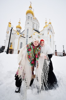 Two little girls in fur coats and shawls in russian style against the surface of a christian church