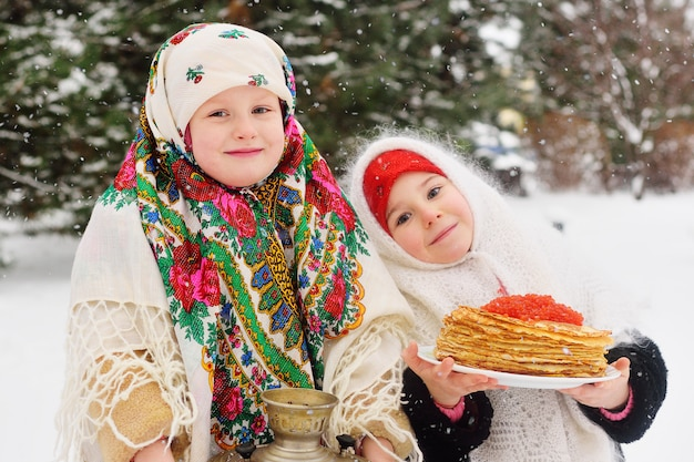 Two little girls in fur coats and shawls in russian style on his head
