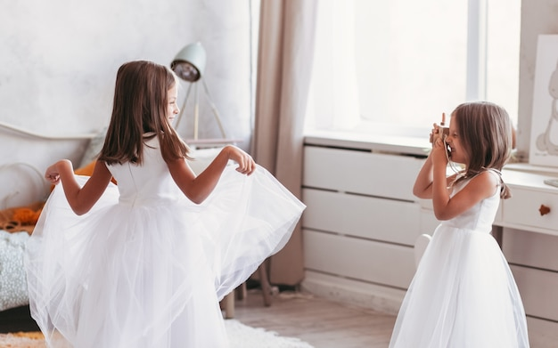 2人の少女のガールフレンドが明るい部屋で楽しく遊んでいます。一緒にフレンドリーな姉妹