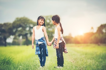 Two little girls hand holding together having fun in the park