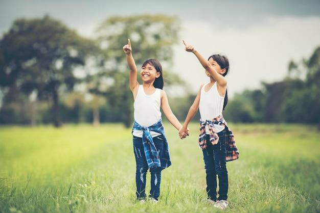 2つの小さな女の子が一緒に公園で楽しいを持って手を