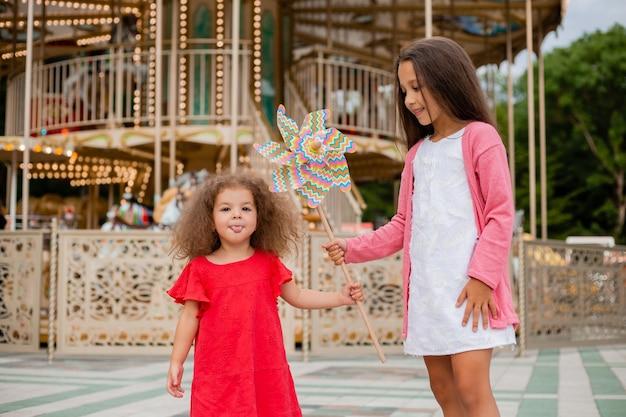 Две маленькие девочки в парке развлечений играют в игрушечный ветерок