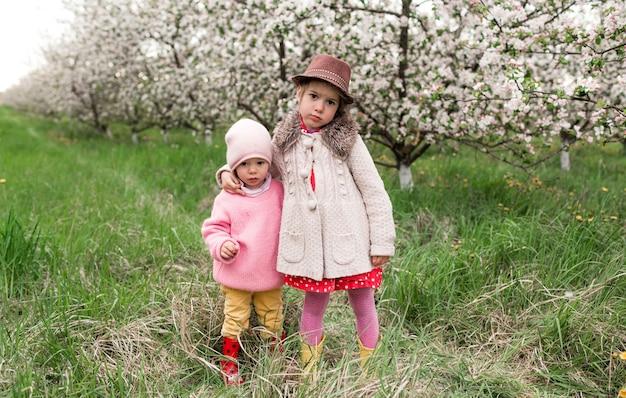 明るい服と帽子をかぶった二人の少女が、咲く庭で抱き合っています。春の気分。
