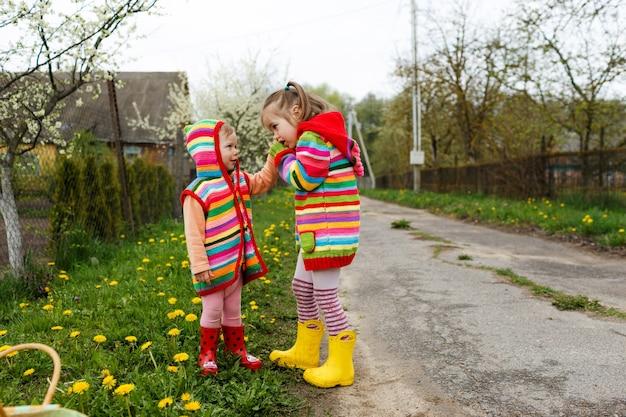 밝은 옷을 입은 두 소녀가 노란 민들레 사이에서 서로의 손을 잡고 있습니다. 행복한 어린 시절.