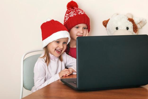 노트북 모니터를 보고 부드러운 장난감을 가진 크리스마스 모자를 쓴 어린 소녀 두 명