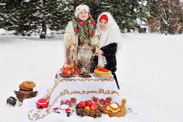 Две маленькие девочки в шубах и платках в русском стиле на своем