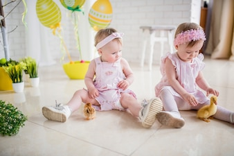Two little girls in pink dresses play on the floor in the studio with Easter decor