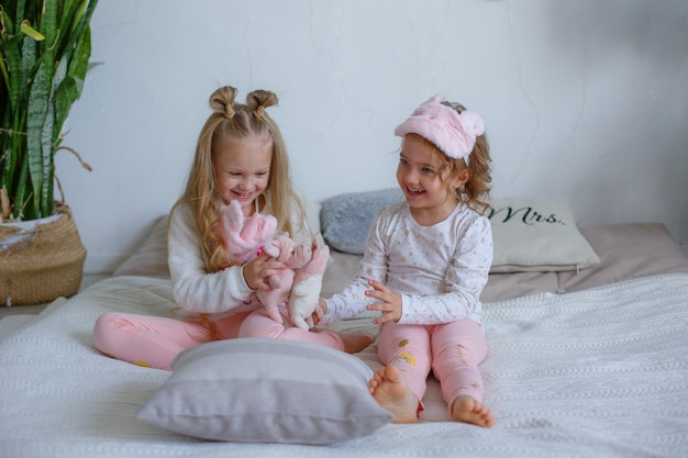 Две маленькие девочки в пижамах сидят на кровати и балуются
