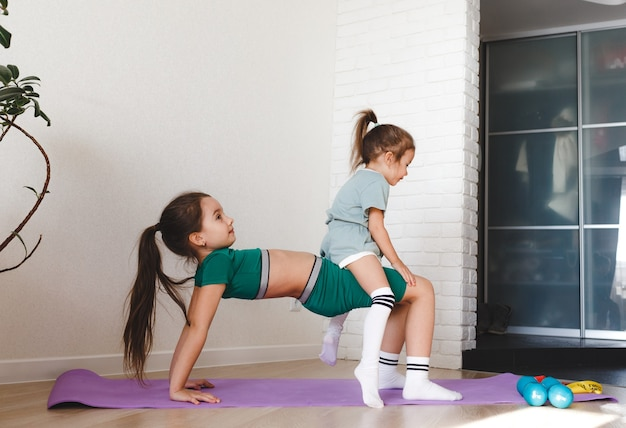 스포츠 유니폼을 입은 두 어린 소녀가 집에서 피트니스에 종사하고 있습니다.