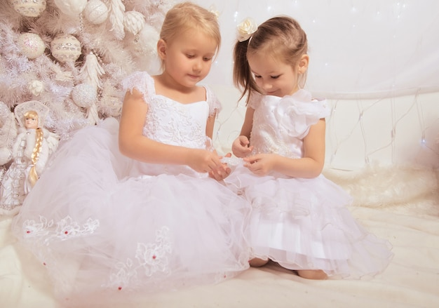 Две маленькие девочки в белых платьях возле елки с новогодним украшением